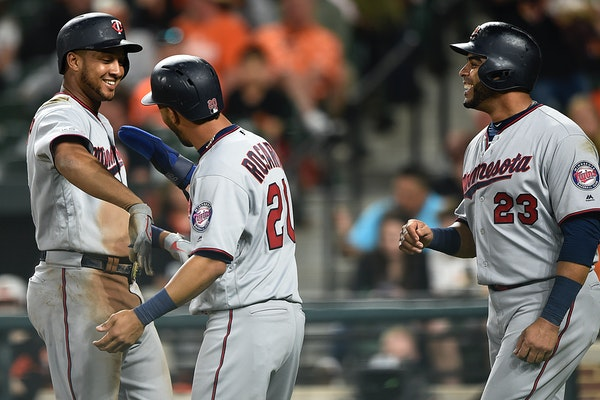 Jonathan Schoop, left, is congratulated by Eddie Rosario, center, and Nelson Cruz after hitting a three-run home run against the Orioles in the fourth