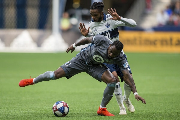 Vancouver Whitecaps' Alhassane Bangoura, rear, plays the ball against Minnesota United's Romain Metanire in the second half of the March 2 match i