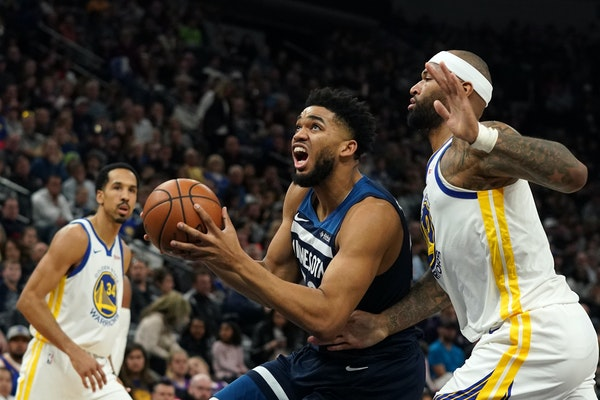 Timberwolves center Karl-Anthony Towns drove to the basket as Warriors center DeMarcus Cousins raced to defend