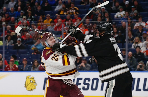 Minnesota Duluth forward Peter Krieger (25) and Providence defenseman Davis Bunz battled in front of several empty seats during the April 11 NCAA Froz