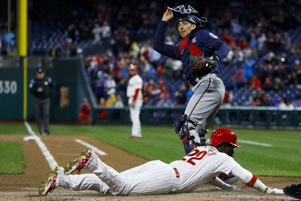 Philadelphia Phillies' Andrew McCutchen, bottom, scores past Minnesota Twins catcher Jason Castro during the first inning of a baseball game Friday,