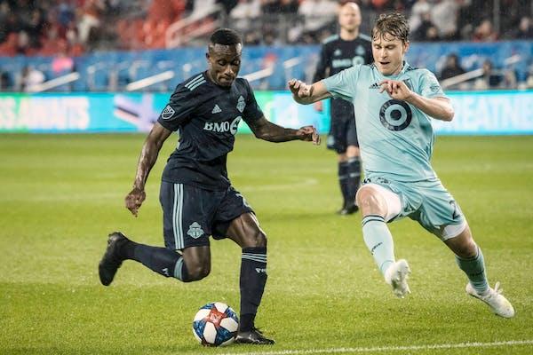 Toronto FC midfielder Richie Laryea (22) battles for the ball against Minnesota United midfielder Rasmus Schuller (20) during Friday's first-half acti