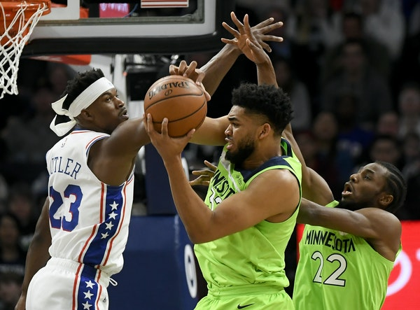 Timberwolves center Karl-Anthony Towns pulled down a defensive rebound against Philadelphia guard Jimmy Butler in the first half Saturday night.