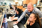 Anoka High teacher Paul Heida helped sophomore Ebony Elliott, bottom right, with illustration software during yearbook class Tuesday. Last year, state