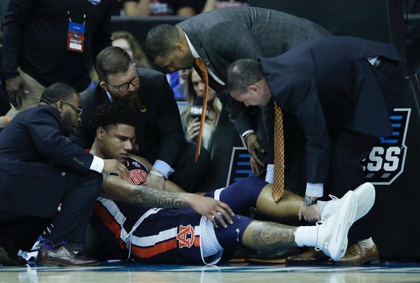 Trainers assist Auburn's Chuma Okeke after he was injured during the second half vs. North Carolina. Okeke tore the ACL in his knee and will undergo s