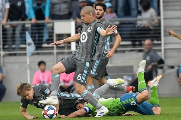 Minnesota United midfielder Rasmus Schuller (20) and Seattle Sounders midfielder Nicolas Lodeiro (10) collided as midfielder Osvaldo Alonso (6) moved
