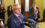 Minnesota Gov. Tim Walz speaks with reporters at the State Capitol Monday during a break in talks with House Democratic and Senate Republican leaders