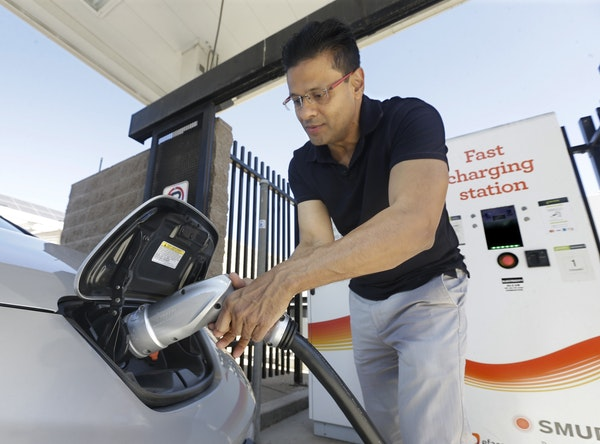 In this Thursday, Sept. 17, 2015 file photo, Darshan Brahmbhatt, plugs a charger into his electric vehicle at the Sacramento Municipal Utility Distric