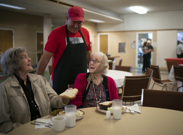 Volunteer Tom Belting visited after he served rib dinners to guests Dolores Schmeidel, left, and Mary Jo Mileski at Loaves & Fishes' Hopkins locatio