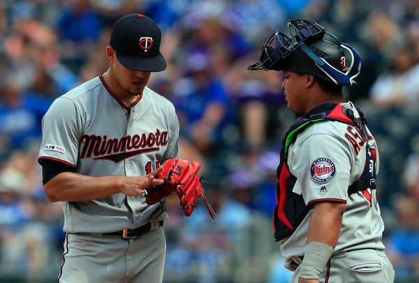 Twins starting pitcher Jose Berrios, left, shows his blistered finger to catcher Willians Astudillo during the eighth inning