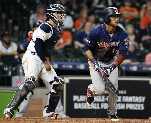 Minnesota Twins' Jorge Polanco, right, watches his two-run home run off Houston Astros relief pitcher Chris Devenski during the eighth inning of a b