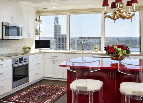 Helene Houle updated her St. Paul condo with a kitchen island in bright cherry red, her favorite color. Clear acrylic chairs let the red Cambria count