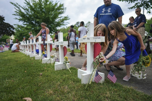Kelly Fowler, a state delegate who represents parts of Virginia Beach, with her daughters Sophie, right, and Tessa at a makeshift memorial for the vic