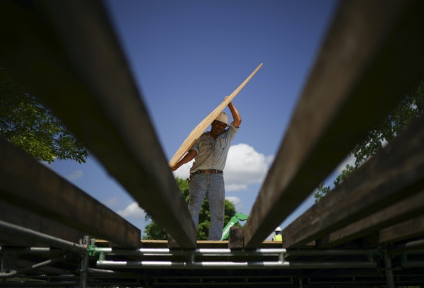 Workers built a walkway at the main entrance to TPC Twin Cities golf course in Blaine on June 6. Thousands pour will into the Anoka County suburb come