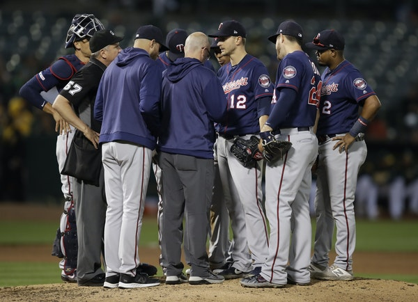 Twins pitcher Jake Odorizzi (12) met with teammates, manager Rocco Baldelli and trainer Tony Leo on the mound in the fourth inning Tuesday night at Oa