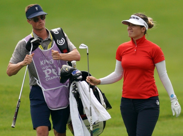 Hannah Green handed off a club to her caddie as she walked down the ninth hole fairway Friday at Hazeltine National.
