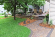 Multi-colored paver patio and walkways, and a boulder fountain with shrubs and perennials, add eye-pleasing interest and beauty to this once bare Minn