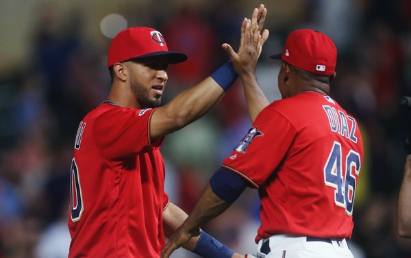 Eddie Rosario, left, goes through the celebration line with a high-five from coach Tony Diaz after the Twins defeated the Oakland Athletics 6-3