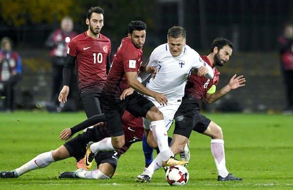 Finland's Robin Lod, second right, vies for the ball with Turkey's Hakan Calhanoglu, left, Ismail Koybasi, center left, Okay Yokuslu, on the groun