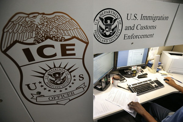 An unidentified Immigration and Customs Enforcement deportation officer reviews forms.