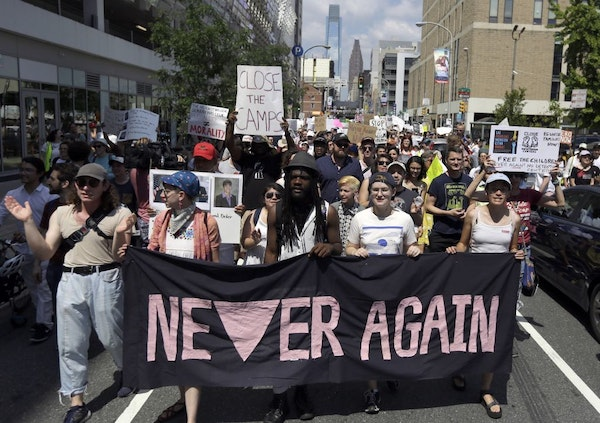 """Protestors assembled by a majority Jewish group called """"Never Again Is Now"""" walk through traffic as they make their way to Independence Mall Thursday"""