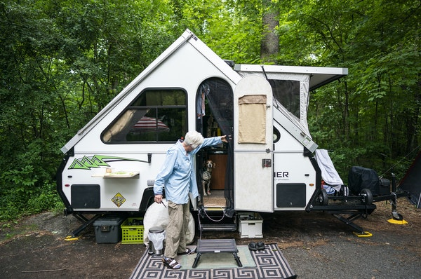 Polly West stands outside her A-frame pop-up camper at William O'Brien State Park.