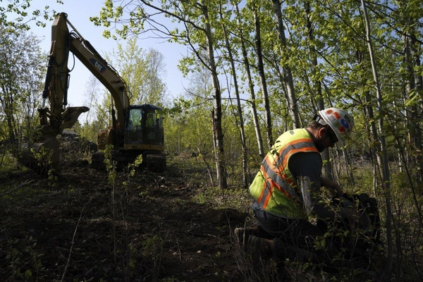 In this Wednesday, May 29, 2019, Eric Olson, right, gathers his tools as contractor Robert Radotich uses a backhoe to dig areas so the soil stratifica