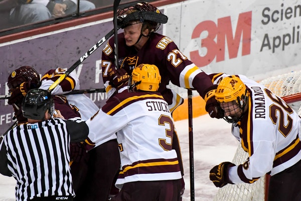 Minnesota-Duluth Bulldogs forward Riley Tufte (27) and Minnesota Golden Gophers forward Darian Romanko (26) tussled during the third period of a game