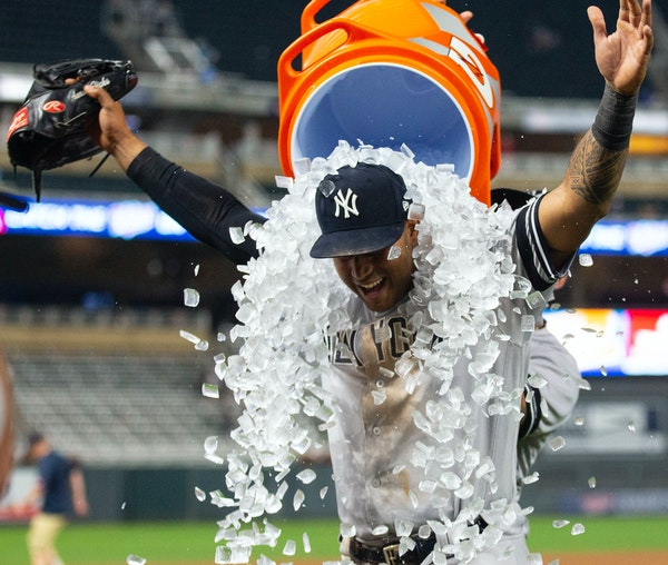 Yankees center fielder Aaron Hicks is doused in an ice bath by a teammate after making the game-winning catch in the bottom of the 10th inning.