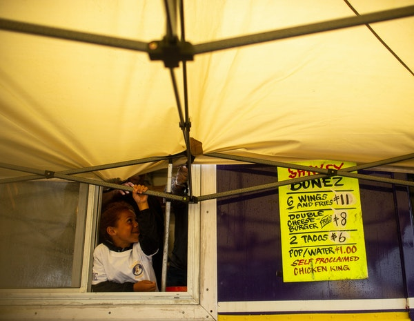 Durall Chappell, 6, helps hold down the tent in front of the Shakey Bonez food truck as the wind picks up Saturday at St. Paul's Rondo Days festival.