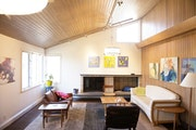 The project included knocking down a wall between the kitchen and living room, (in this photo), adding more lighting and restoring the cedar paneling.