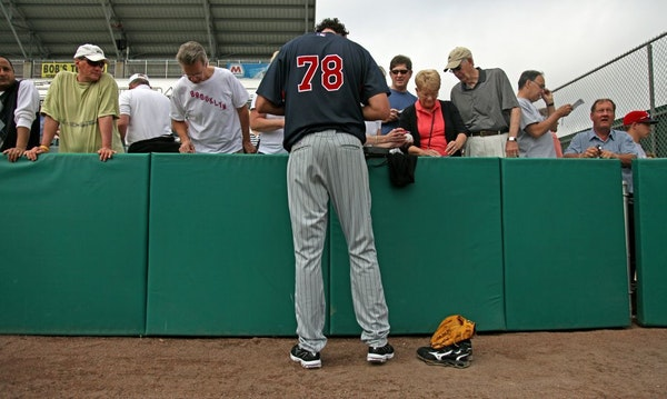 Seven-foot-1 Loek van Mil towered over fans as he stopped to sign autographs at the end of a twins spring training workout in 2010.