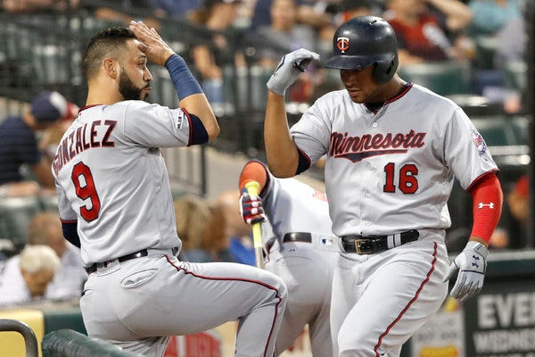 The Twins' Jonathan Schoop celebrates his home run off White Sox starting pitcher Lucas Giolito with Marwin Gonzalez during the second inning