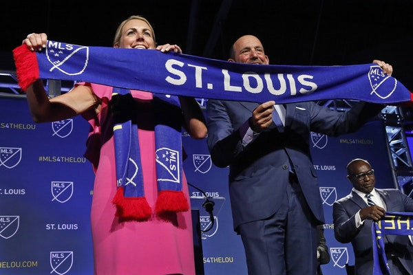 Carolyn Kindle Betz, a member of the ownership group of the new soccer franchise, and Major League Soccer Commissioner Don Garber display a St. Louis