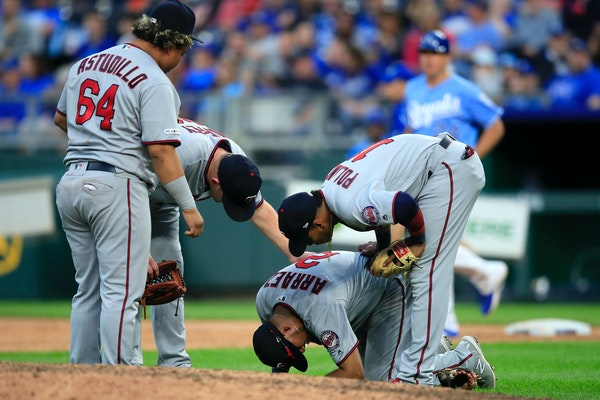 Twins third baseman Luis Arraez is checked on by teammates Willians Astudillo, Jorge Polanco and Tyler Duffey during the seventh inning