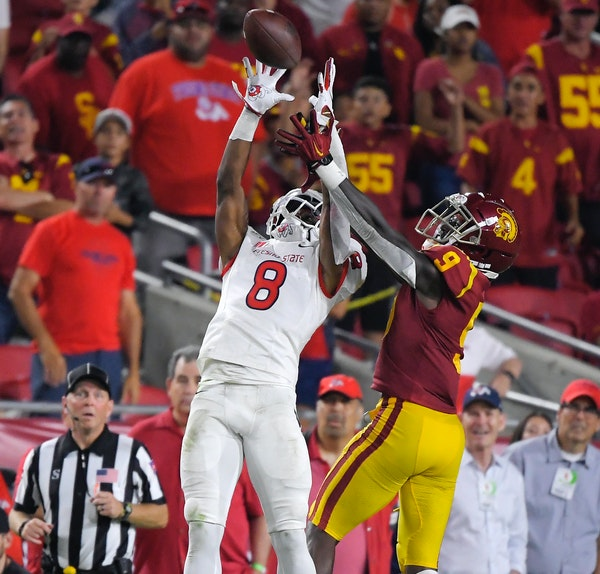 Fresno State wide receiver Chris Coleman, left, catches a pass while under pressure from Southern California cornerback Greg Johnson