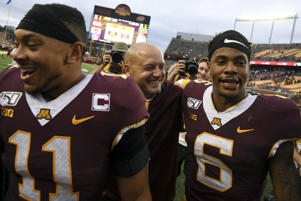 Gophers coach P.J. Fleck walked off the TCF Bank Stadium field with Antoine Winfield Jr. (11) and Chris Williamson (6) after the team's comeback ove