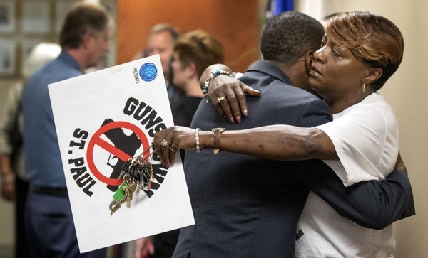 St. Paul Mayor Melvin Carter hugged Dora Jones-Robinson at police headquarters after speaking during a news conference Tuesday in response to the rece