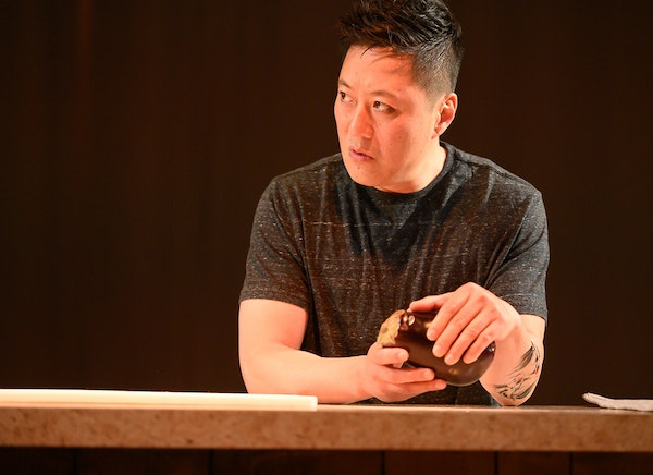"""Kurt Kwan contemplates an eggplant in """"Aubergine,"""" playing at Park Square Theatre."""