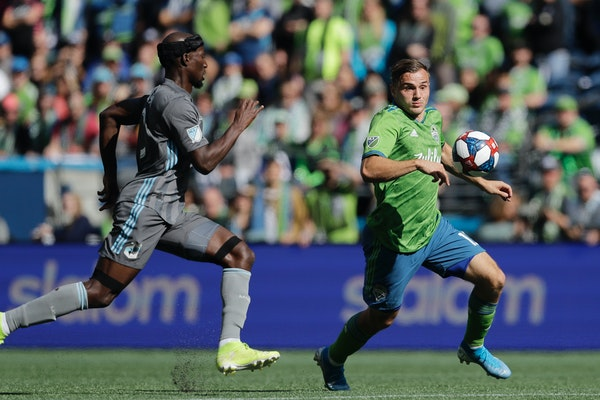 Seattle Sounders forward Jordan Morris, right, eyes the ball as Minnesota United's Ike Opara, left, closes in during the first half