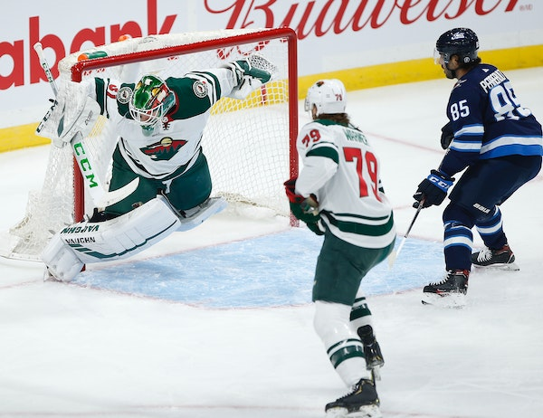 Wild goaltender Kaapo Kahkonen saved this shot from Winnipeg's Mathieu Perreault during the first period but by then the Jets already had a 2-0 lead.