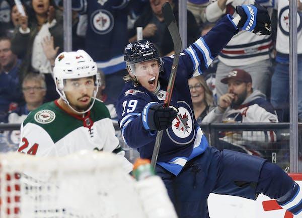 Winnipeg's Patrik Laine celebrated his goal as Wild defenseman Matt Dumba skates by him during the second period.
