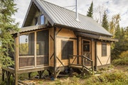 The 600-square-foot off-the-grid timber frame cabin includes a sleeping loft above the living area.
