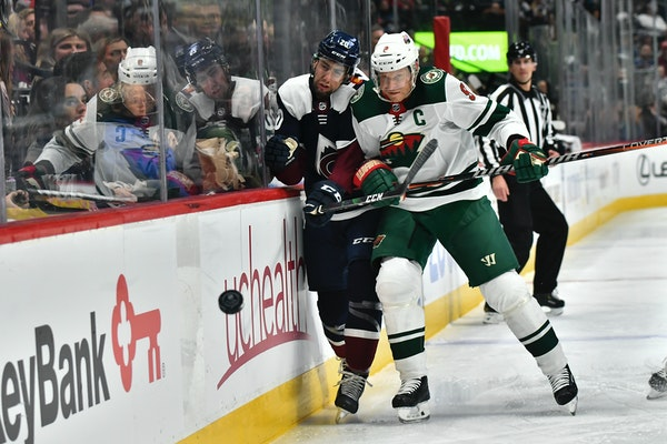 Wild center Mikko Koivu pounds Avalanche defenseman Conor Timmins into the boards during the first period