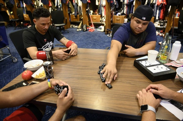 Infielder Ronald Torreyes and catcher Willians Astudillo are among a foursome playing dominoes in the clubhouse before the start of a game against the