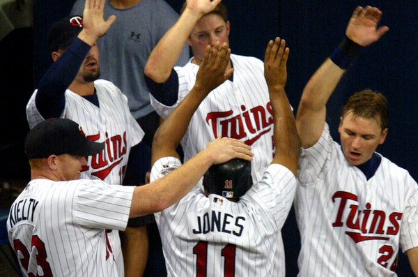 Jacque Jones (11) got a little recognition from his teammates after scoring in Game 4 of the 2002 American League Division Series against the Oakland