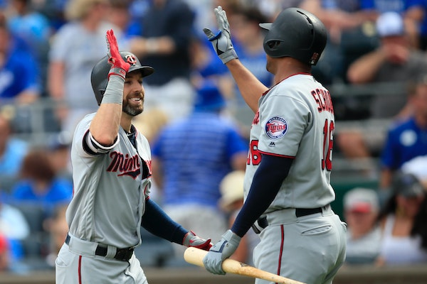The Twins' Jake Cave, left, is congratulated by teammate Jonathan Schoop, right, following his solo home run during the first inning