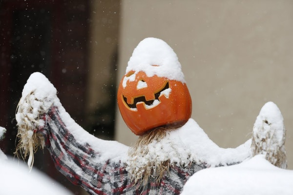Snow covers a pumpkin used as part of a Halloween display outside a Denver-area home.
