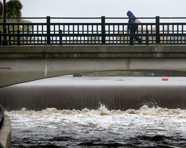 High water cascaded over the Ames Mill Dam on the Canon River as a pedestrian crossed the South Water Street Bridge on Wednesday in Northfield, Minn.