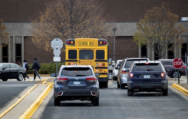 A police vehicle pulled up to Bloomington Jefferson High School while cars waited to pick students.